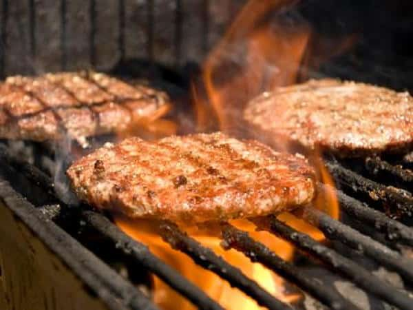 juicy burgers on grill over flames